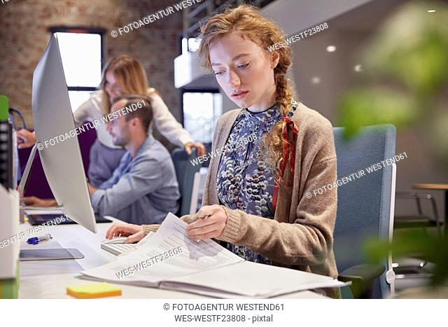 Young woman working in modern creative office, usine laptop