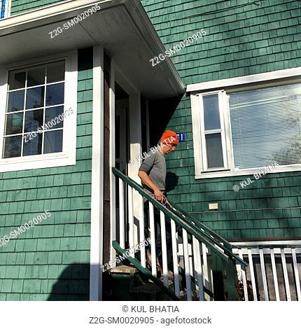 A man walks down the steps of a green wooden house, Halifax, Nova Scotia, Canada. Wood-frame homes, with cedar siding which is painted in many colours