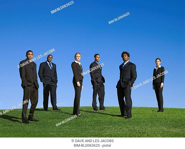 Business people standing outdoors in grass