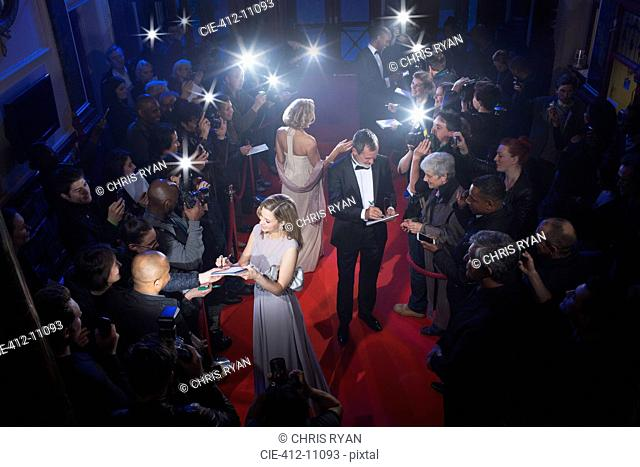 Well dressed celebrities signing autographs on red carpet