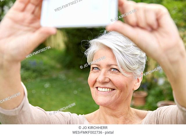 Portrait of smiling woman taking selfie with smartphone