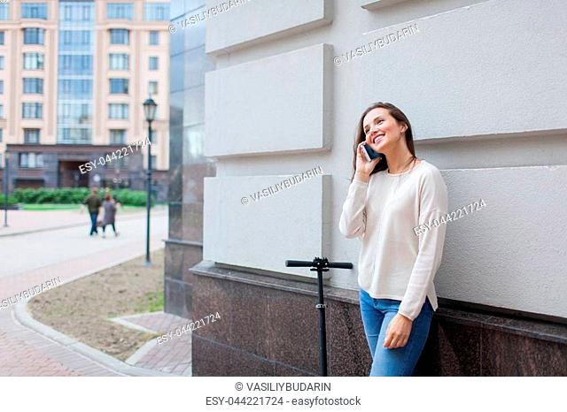 Beautiful young girl with long brown hair stopped while riding the scooter, to call a friend on the phone on the background of the gray wall