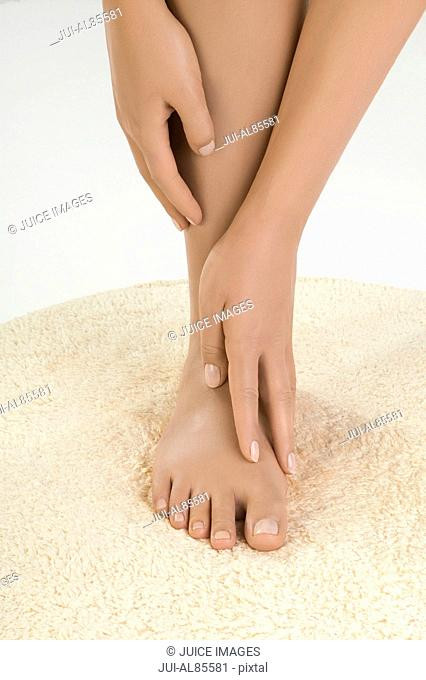 Close up of woman's hands caressing bare foot on rug
