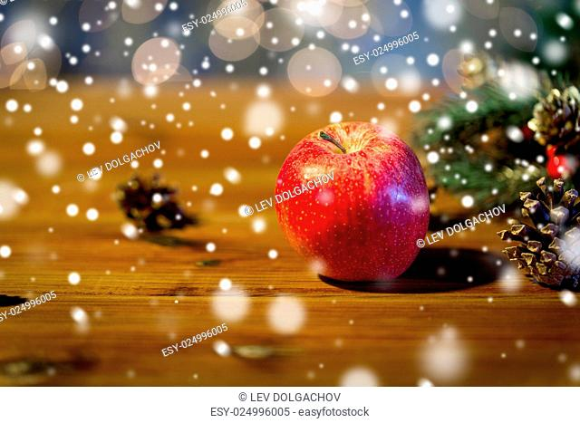 christmas, decoration, holidays and new year concept - close up of red apple with fir branch decoration on wooden table