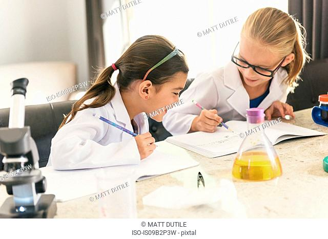Girls doing science experiments writing in notebooks