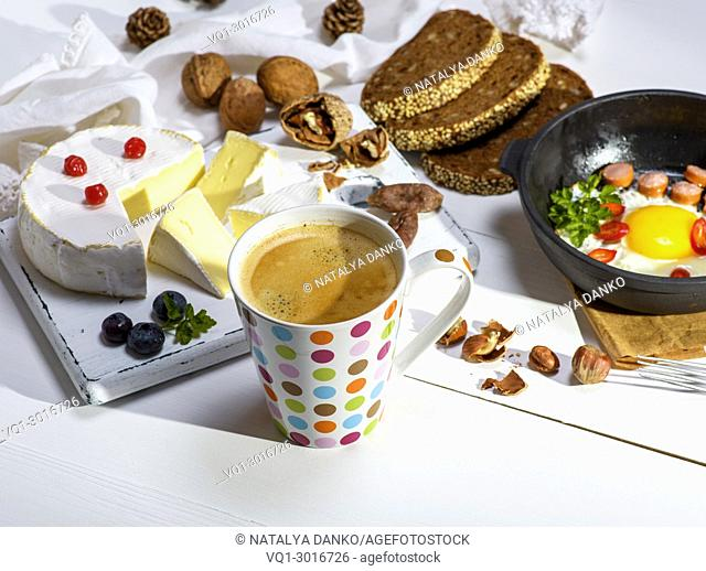 black coffee with brown foam in a white ceramic mug in colorful polka-dot, behind a round camembert cheese and a black frying pan with a fried egg