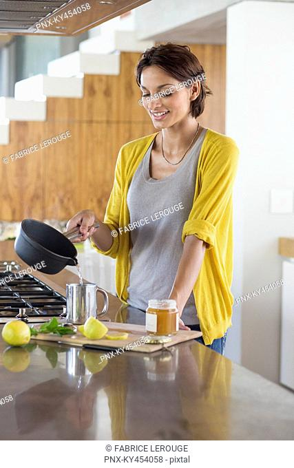 Woman preparing herbal tea in the kitchen