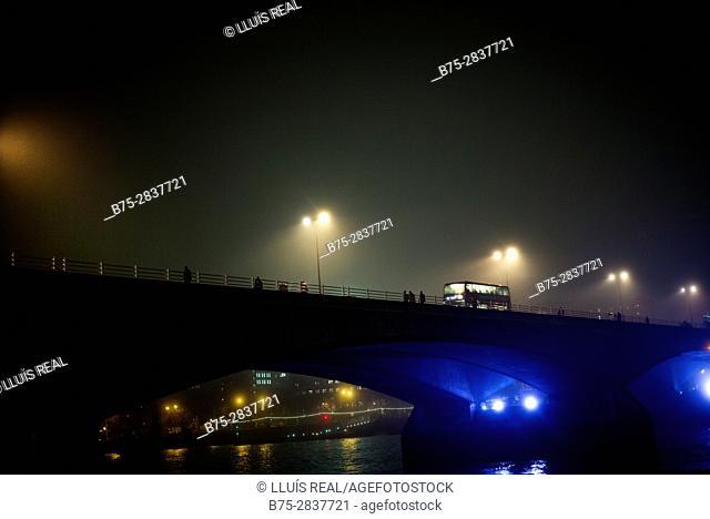 Vista nocturna de un puente con farolas encendidas, gente andando, un autobus circulando en una noche de niebla. Waterloo Bridge, West End, River Thames