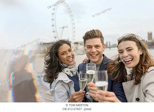 Portrait enthusiastic, smiling friends celebrating, toasting champagne near Millennium Wheel, London, UK