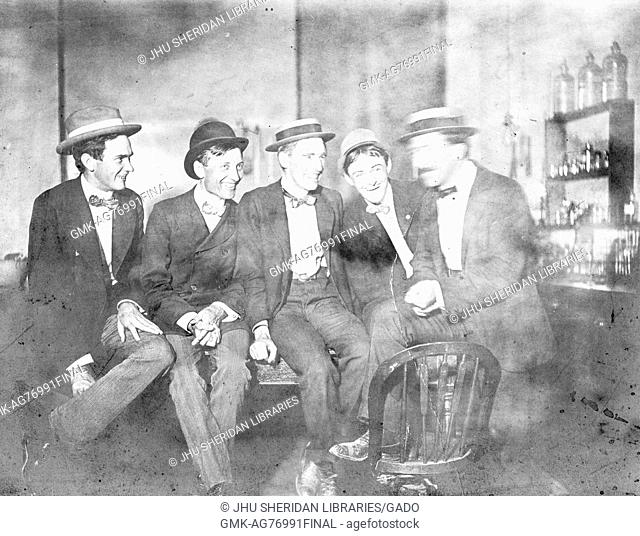Group photograph of 1901 Johns Hopkins University PhDs in a laboratory, wearing skimmer hats and sitting in a row on a table, with smiling facial expressions