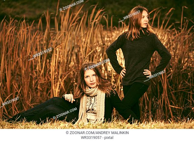 Two happy young fashion girls on nature