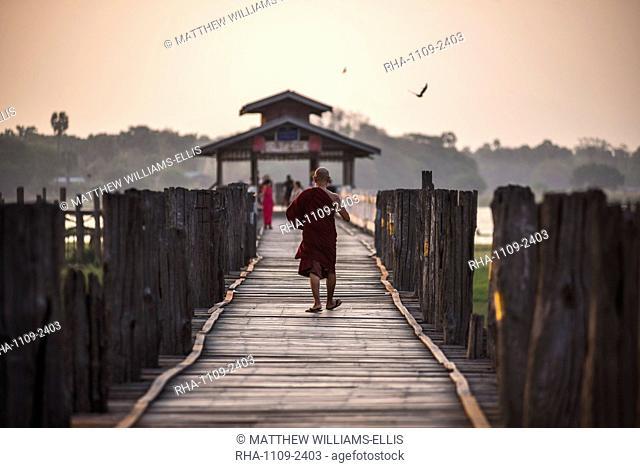 Buddhist Monk on U Bein Teak Bridge at sunrise, Mandalay, Mandalay Region, Myanmar (Burma), Asia