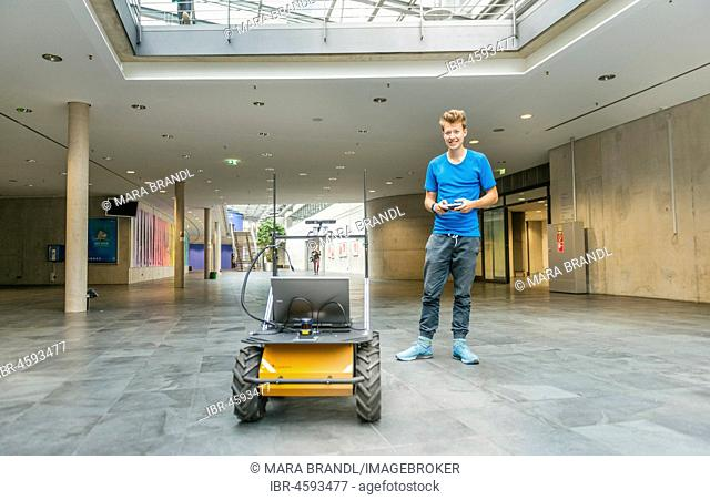 Student with robot Auto Husky of the company Clearpath, autonomic driving, University of Applied Sciences Munich, Bavaria, Germany