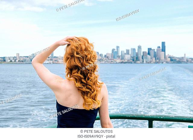 Rear view of woman looking at skyline from passenger ferry on Puget Sound, Seattle, USA