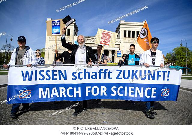 14 April 2018, Germany, Munich: Protestors start their march at the Koenigsplatz and carry a banner reading 'Wissen schafft Zukunft! March for Science' (lit