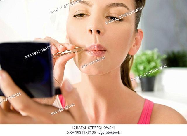 Woman plucking her facial hair