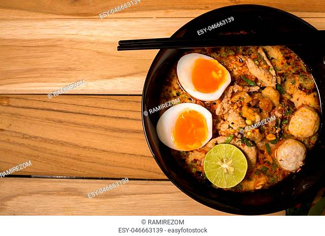 bowl of noodles with vegetables and soft boiled egg on wooden table. delicious noodle. Instant noodle. hot noodle.Homemade Quick Ramen Noodles with egg