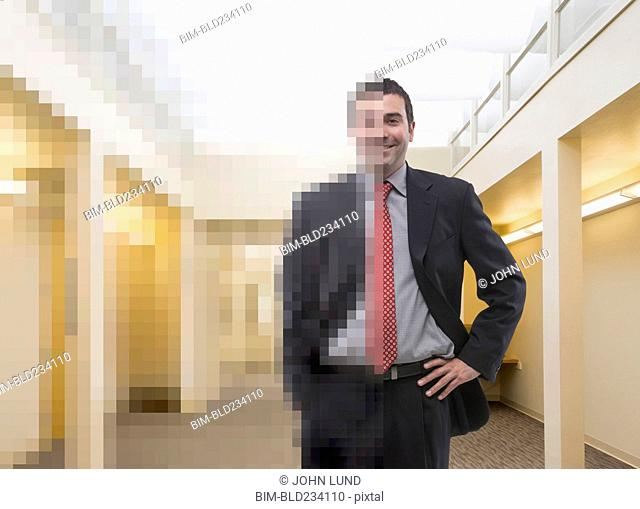 Partially pixelated Caucasian businessman in office corridor
