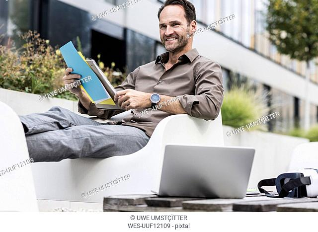 Smiling businessman with document, laptop and Virtual Reality Glasses sitting on terrace