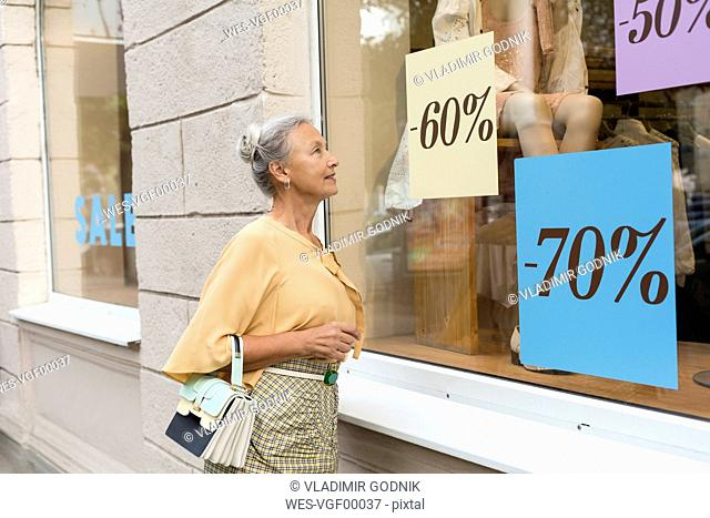 Smiling senior woman looking in shop window of a boutique