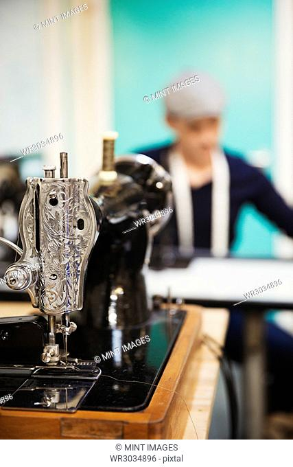 A retro style traditional sewing machine with chased metalwork, and a tailor working in the background
