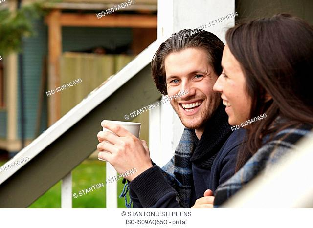 Young couple sitting on porch step drinking coffee