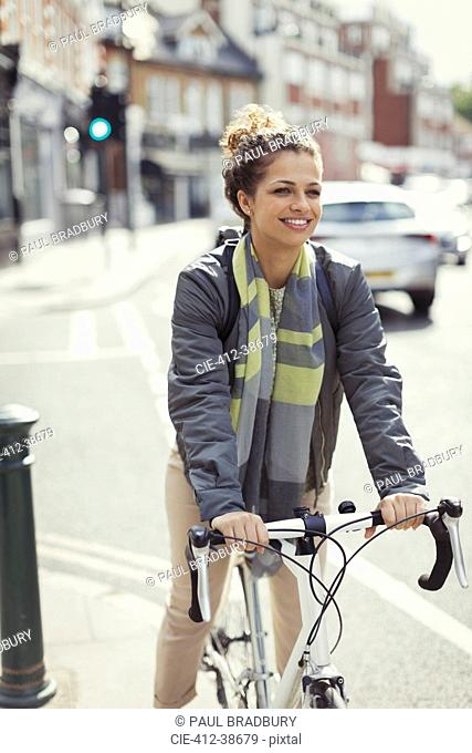 Smiling young woman commuting, riding bicycle on sunny urban street