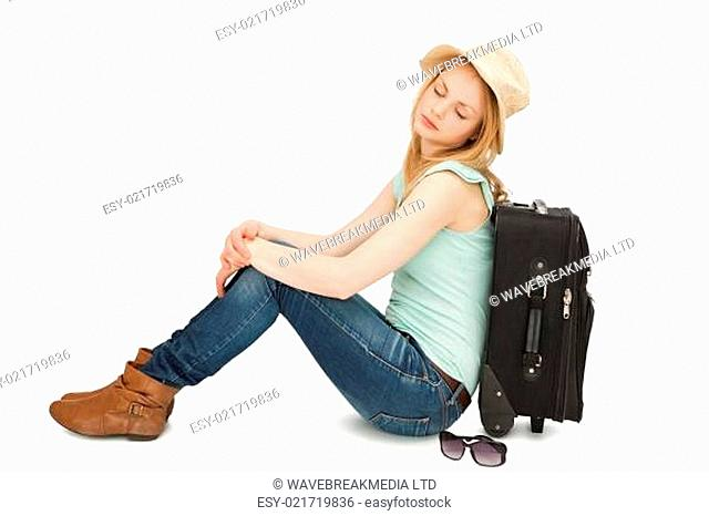 Tired woman sitting against a suitcase