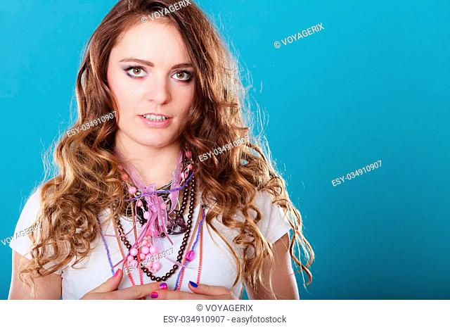 Pretty young woman wearing many plenty of jewelry necklaces beads. Portrait of gorgeous fashion girl in studio on blue