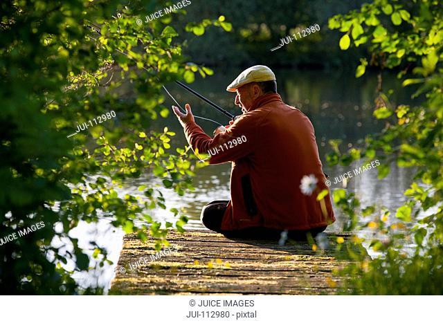 Fisherman casting fishing rod from lakeside dock