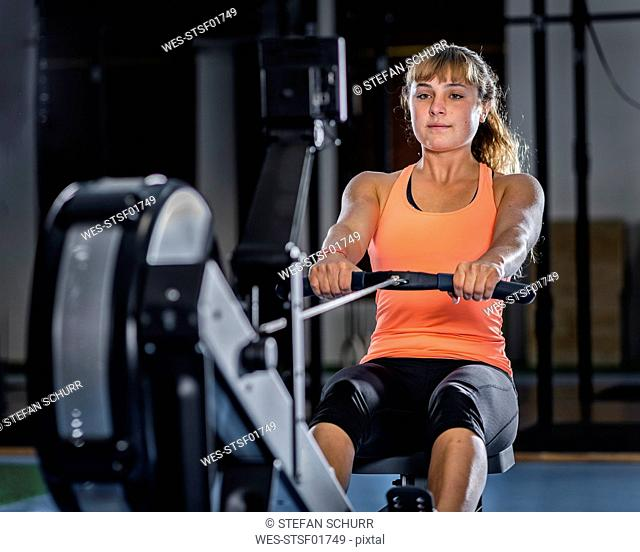 Athletic young woman exercising with rowing machine at gym