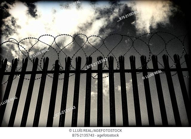 Fence with thorns and stormy sky in London, England, UK, Europe