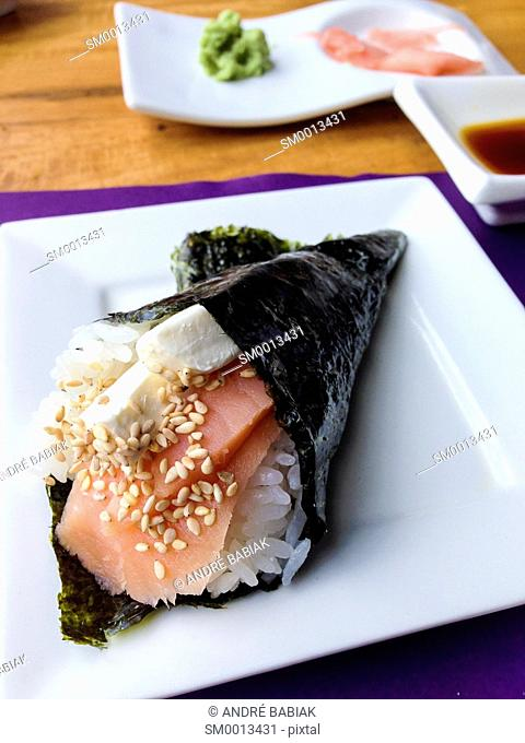 Sushi hand roll filled with raw salmon, rice, cream cheese and sesame seeds in front of ginger with wasabi and soy sauce. Japanese dish