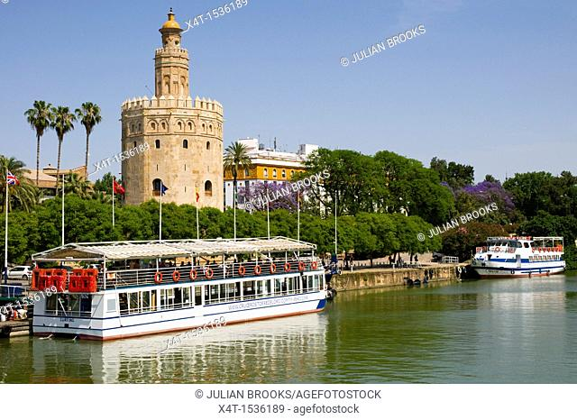 A tourist cruiser moored in front of the Torre del Oro, or Gold tower, in Seville, Andalusia, Spain