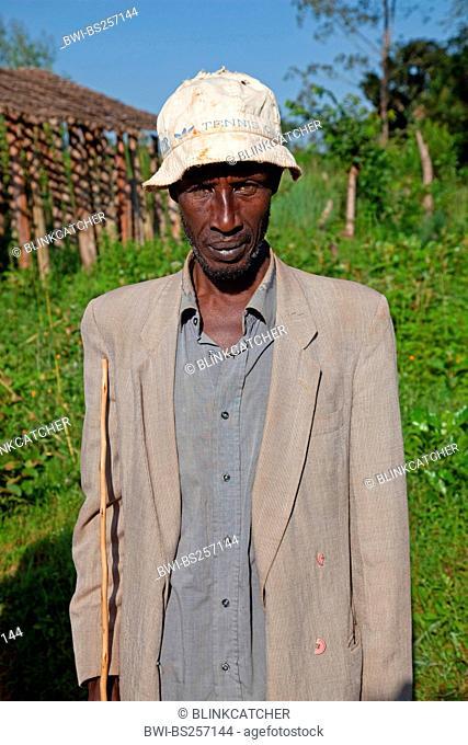 portrait of an elderly Tutsi man with jacket, hat and walking stick, Burundi, Cankuzo, Near National Parc de la Ruvubu, Cankuzo