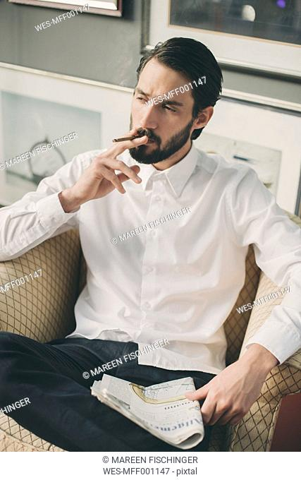 Portrait of young man smoking cigarillo