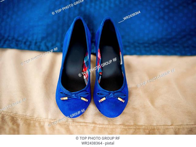 Female elegance bridal blue shoes on beige cloth in horizontal orientation, nobody. Pair of chamois leather wedding shoes with bows