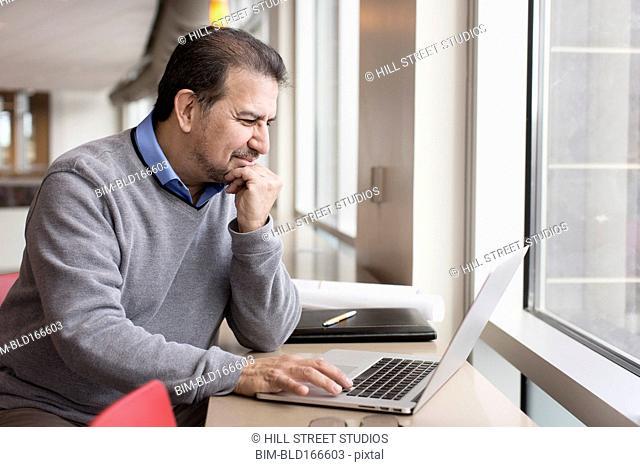 Hispanic man using laptop near window