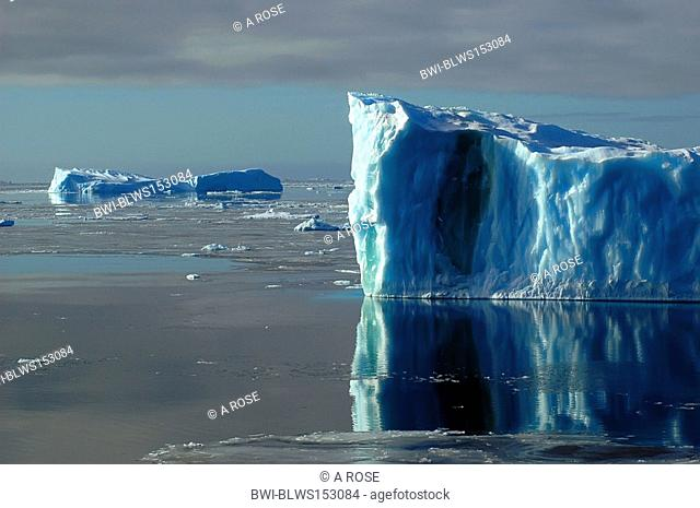 One side of a blue Antarctic iceberg in the Southern Ocean on a nearly flat sea covered by ice floes, Antarctica, Southern Ocean