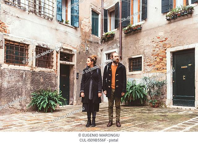 Couple in courtyard looking in opposite directions, Venice, Italy