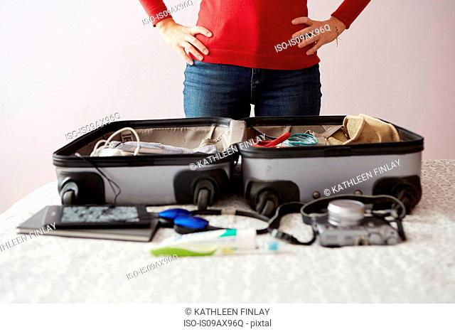 Woman packing suitcase, hands on hips, mid section