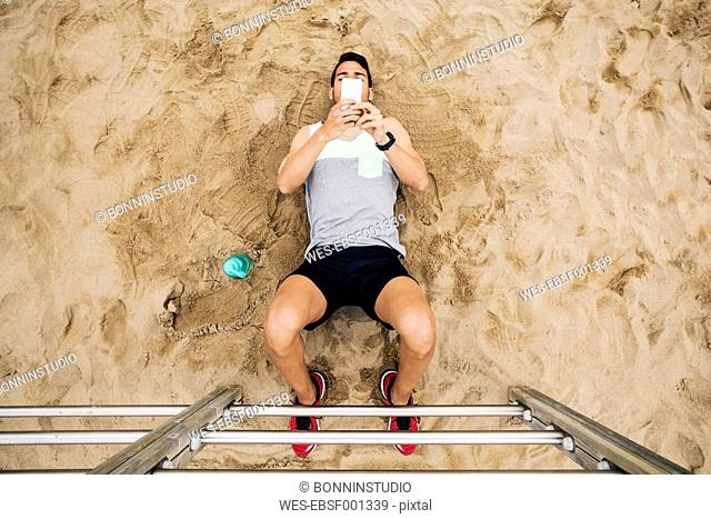 Young man resting at wall bars on the beach looking at cell phone