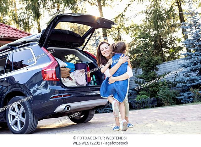 Mother and daughter embracing in front of their car