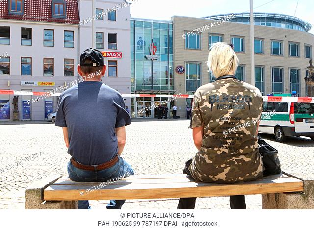 24 June 2019, Saxony-Anhalt, Halberstadt: Curious visitors sit behind a police barrier near the Rathaus-Passage. After a bomb threat in the city centre of...