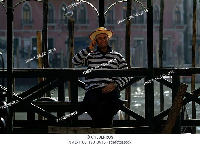 Gondolier talking on a mobile phone and sitting on a bench, Venice, Veneto, Italy