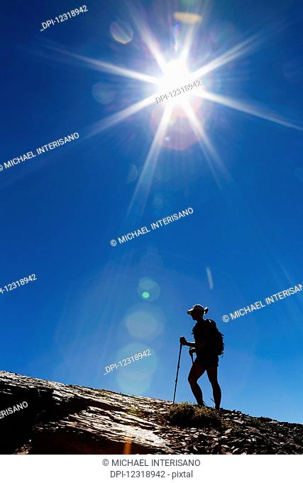 Silhouette of female hiker on rocky ridge with blue sky and sunburst; Waterton, Alberta, Canada