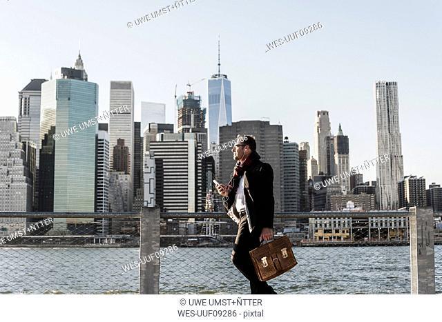USA, Brooklyn, businessman with briefcase standing in front of Manhattan skyline