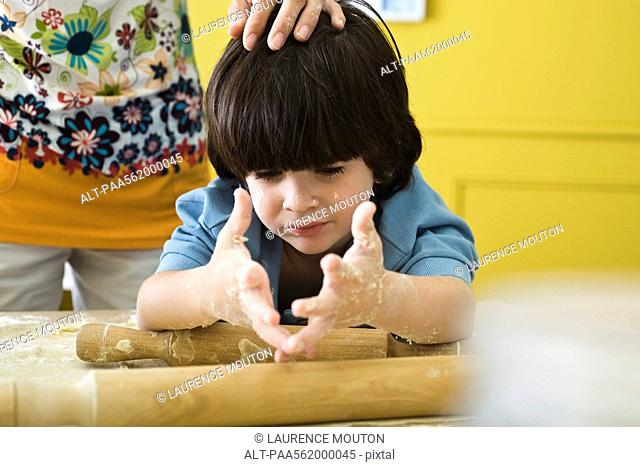 Little boy with messy hands baking with mother, cropped