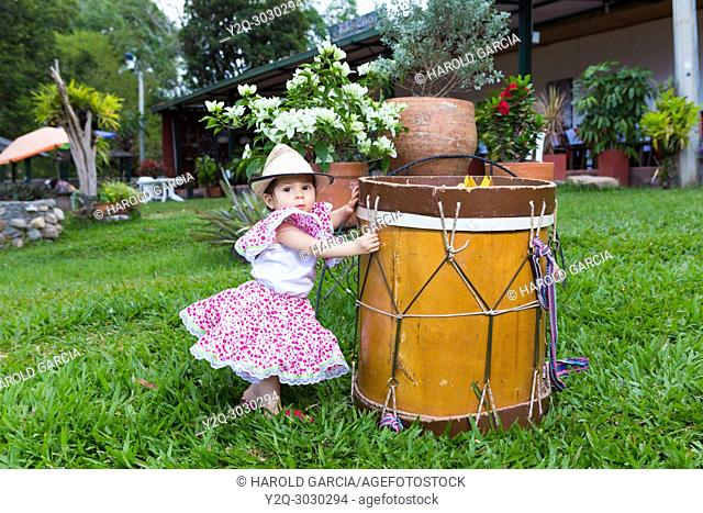 little girl in traditional dance dress with hat next to a drum