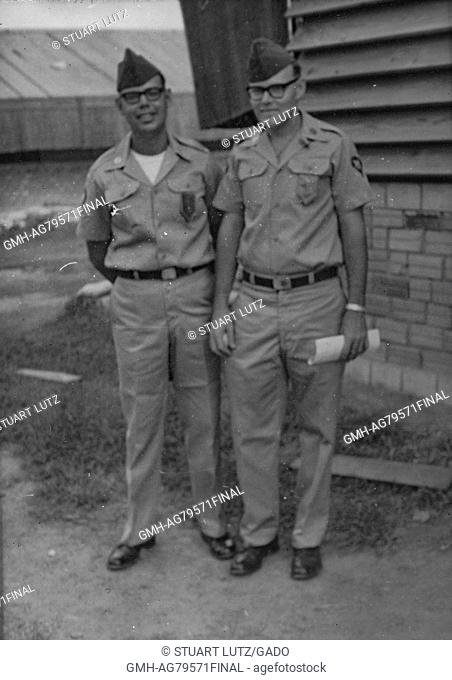 A photograph of two United States Army servicemen wearing their uniforms and garrison caps, the soldier on the right holds papers in his hand